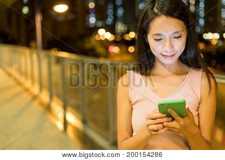 Woman working on mobile phone at night
