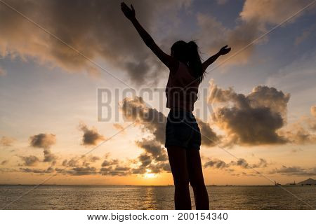 Silhouette of woman hand up under sunset