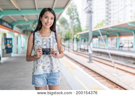 Young asian Woman holding digital camera in light rail station