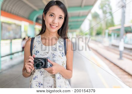 Woman holding digital camera in light rail station