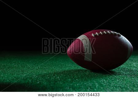 Close-up of American football on artificial turf against black background