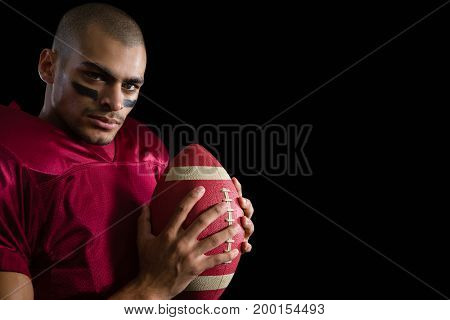 Determined American football player holding a football with both his hands against a black background