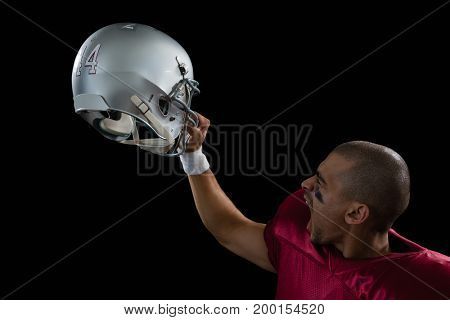 Energetic American football player holding a head gear raised against a black background