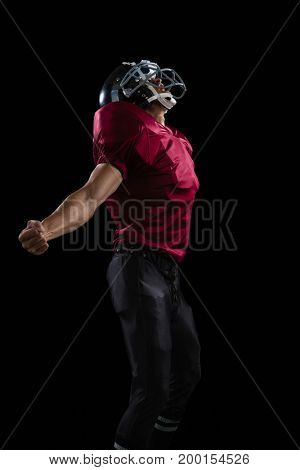 American football player posing with arms stretched open against black background
