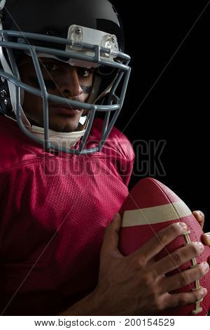 Portrait of American football player holding a football with both his hands