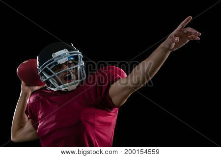 Energetic American football player aiming a ball against a black background