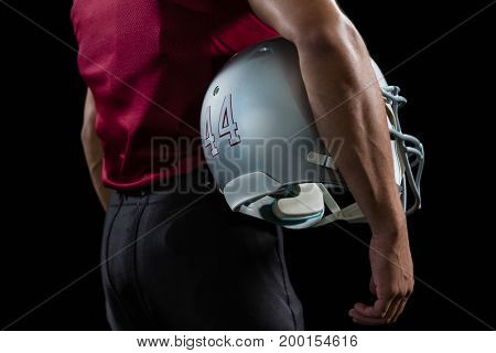 Rear view of American football player holding a head gear under his arms