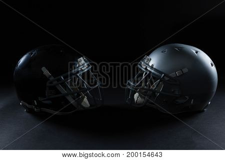 American football head gear facing each other against a black background