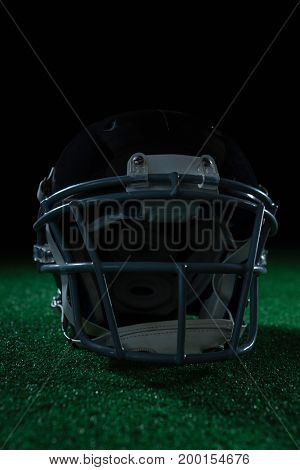 American football head gear on artificial turf against a black background