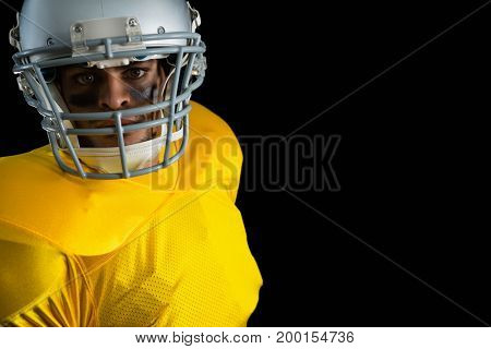 American football leaning on headgear against black background