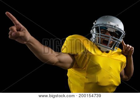 American football player cheering with both his hands raised against a black background