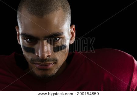 Portrait of determined American football player against a black background