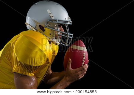 American football player holding a ball close to his face against a black background