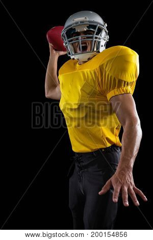 Energetic American football player holding a ball in one hand against a black background
