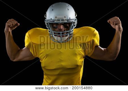 Portrait of American football player flexing his muscles against a black background