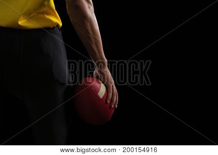Mid section of American football player holding a ball