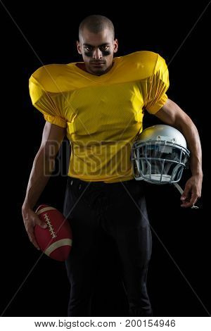 Portrait of American football player holding a ball and head gear