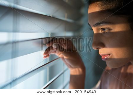 Close-up of thoughtful young woman looking through window blinds