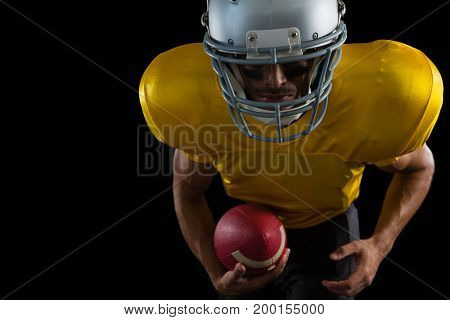 Mid section of American football player leaning forward holding a ball