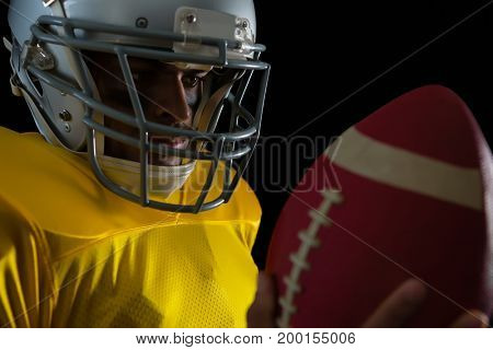 Close-up of American football player looking at football in his hand