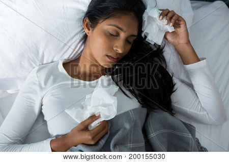 High angle view of sick young woman sleeping on bed at home