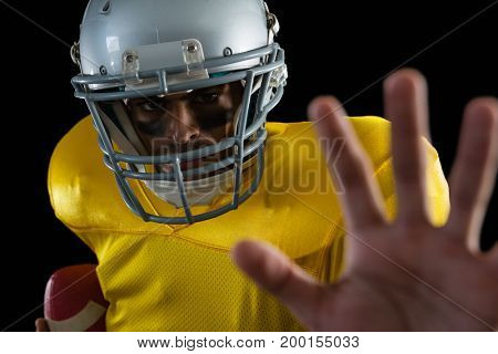 Portrait of American football player holding a ball and gesturing a hand stop sign