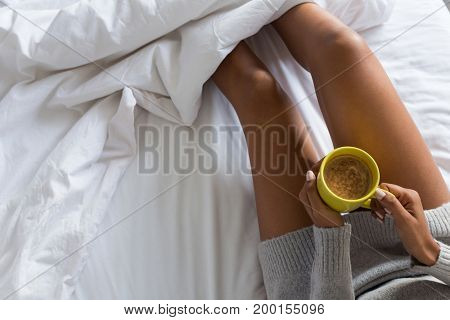 Midsection of woman holding coffee mug while relaxing on bed