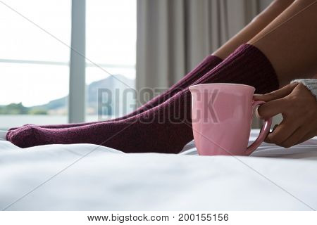 Low section of woman with coffee cup relaxing on bed at home