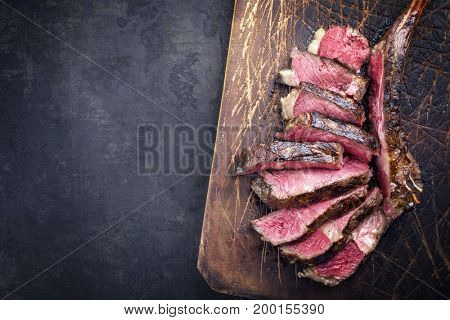 Barbecue dry aged wagyu tomahawk steak sliced as close-up on old wooden board