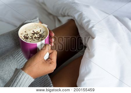 Cropped image of woman having coffee while relaxing on bed at home