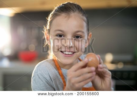 Close-up of smiling girl holding eggs with flour on her nose in the kitchen