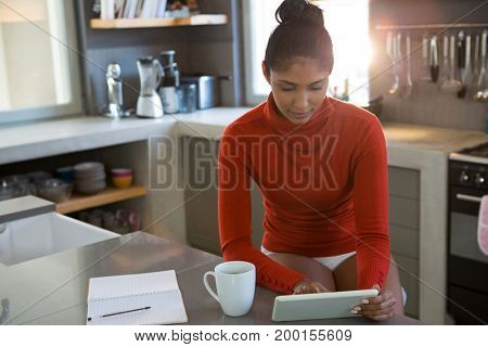 Young woman with coffee mug using digital tablet in kitchen