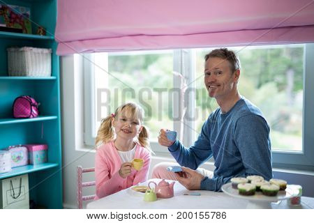 Portrait of father and daughter playing a tea set role play in her room
