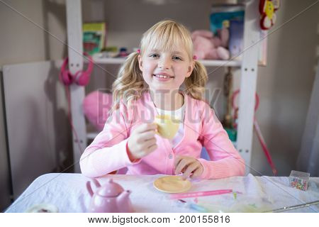 Portrait of cute girl having tea while playing with from the toy kitchen set