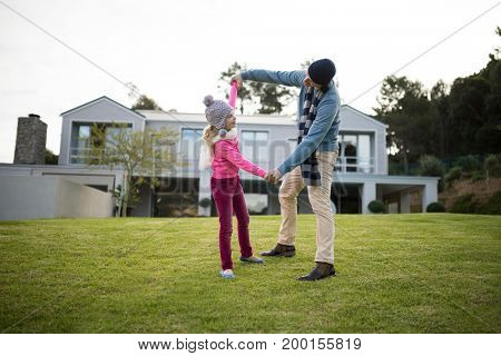 Happy father and daughter dancing in the garden