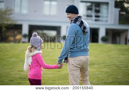Smiling daughter and father holding hands in the garden