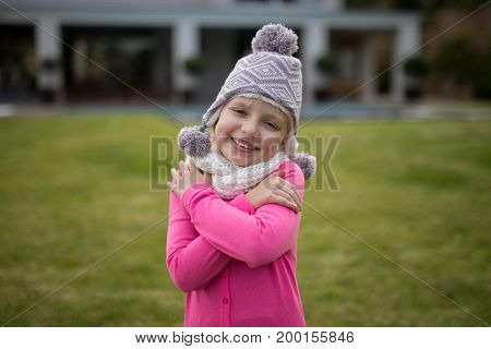 Smiling cute girl in warm clothing standing in the garden