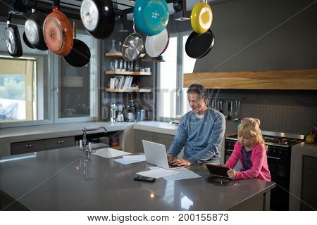 Father using a laptop while daughter is using a tablet in the kitchen