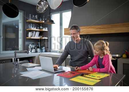 Father using a laptop while daughter is coloring in the kitchen