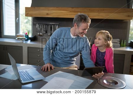 Father and daughter looking at each other and smiling in the kitchen