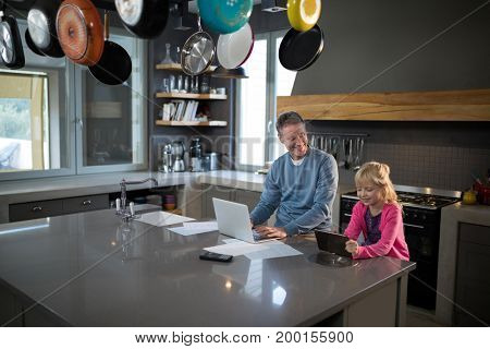 Father looking at daughter while using a tablet in the kitchen
