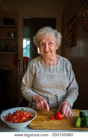 An elderly woman chops vegetables for a salad in the kitchen.
