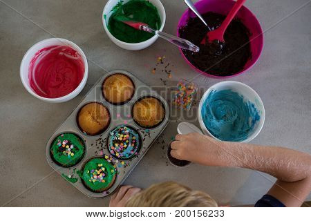 Cropped hand of boy decorating cupcakes with sprinklers at kitchen counter