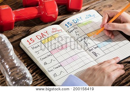 Close-up Of A Person Making Exercise Plan On Notebook Over Wooden Desk