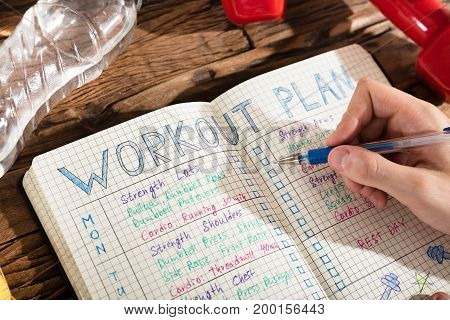 Elevated View Of A Person Making Note Of Workout Plan On Notebook With Exercise Equipment