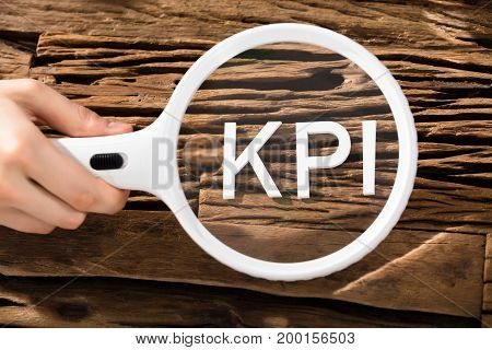 Close-up Of A Human Hand Examining Key Performance Indicator With Magnifying Glass Over Wooden Desk