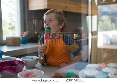Boy holding green batter on spatula seen through glass in kitchen at home