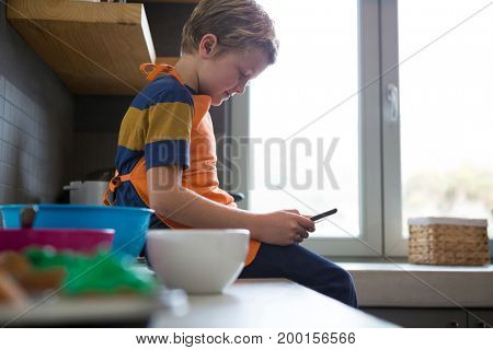 Side view of boy using digital tablet at kitchen counter