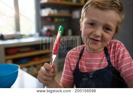 Portrait of boy holding spatula with batter in kitchen at home