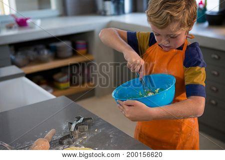 Boy mixing batter in bowl at kitchen